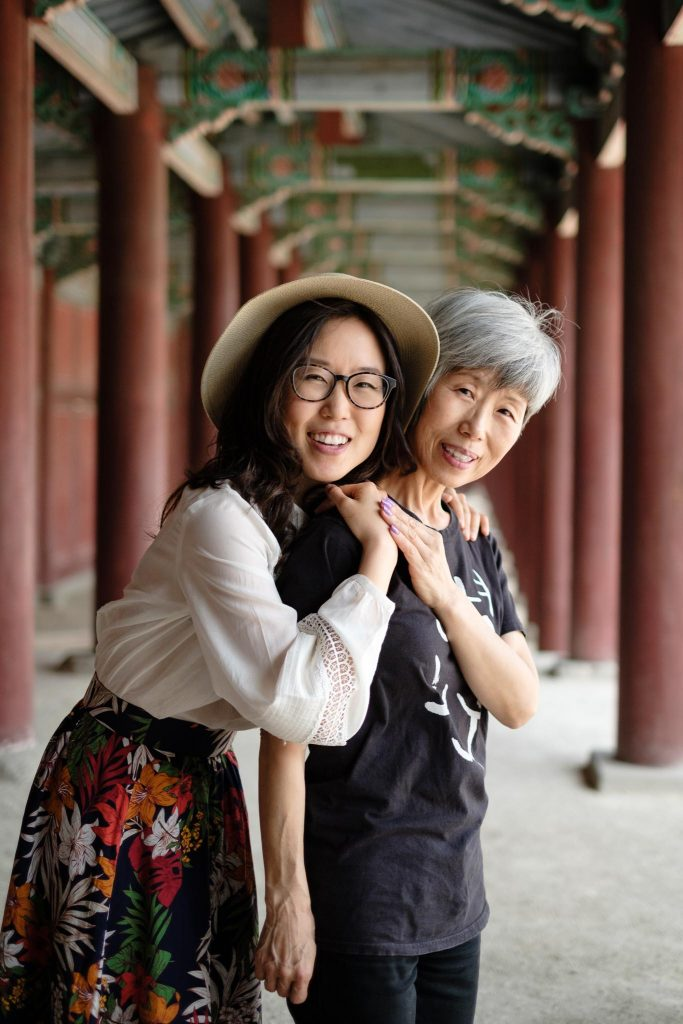 A photo of Miss Mina and Mommy Oh at Changyeongung. They are standing in between columns of the temple.