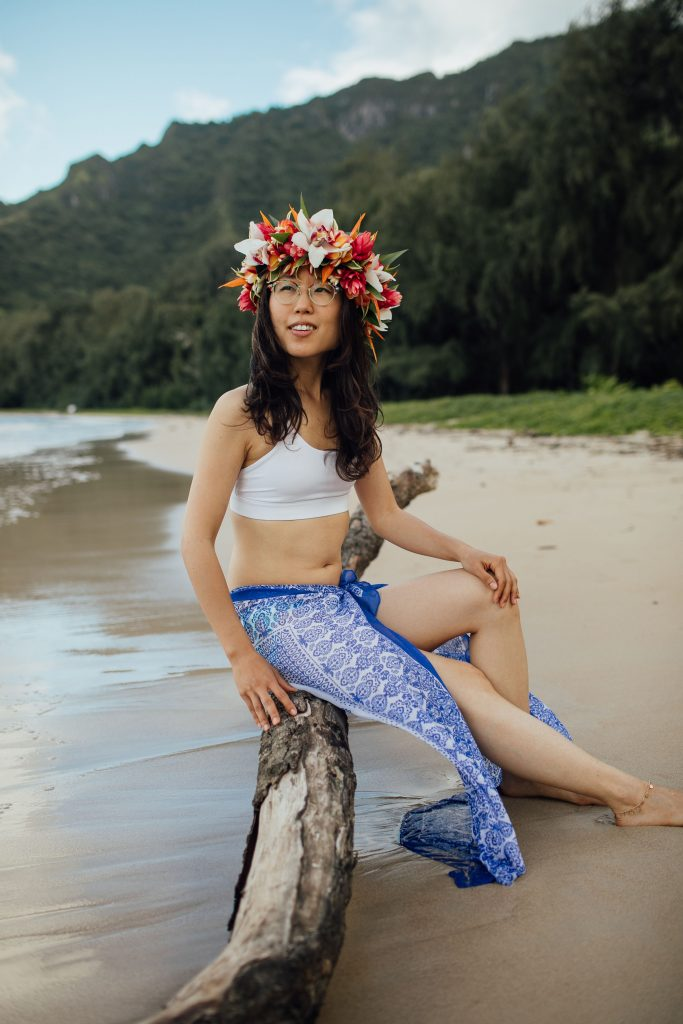 Miss Mina seated by the Ocean in Oahu, with a stunning floral crown on her head.