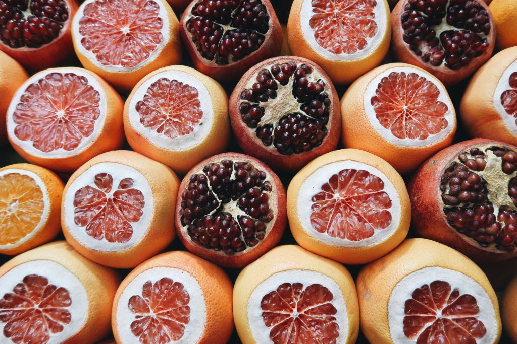 A photo of grapefruits, pomegranates, and oranges - their tops are cut off and you can see their insides. This was in Turkey.