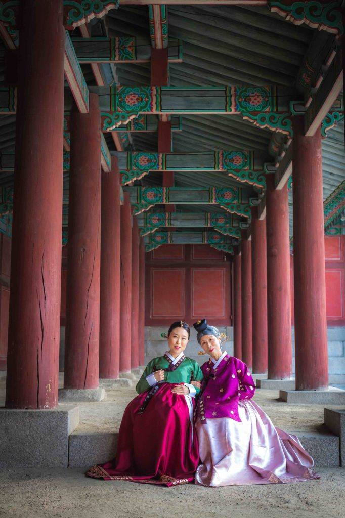 Miss Mina and Mommy Oh in Seoul - taking a photo at a palace. They sit together, dressed in colourful hanbok.