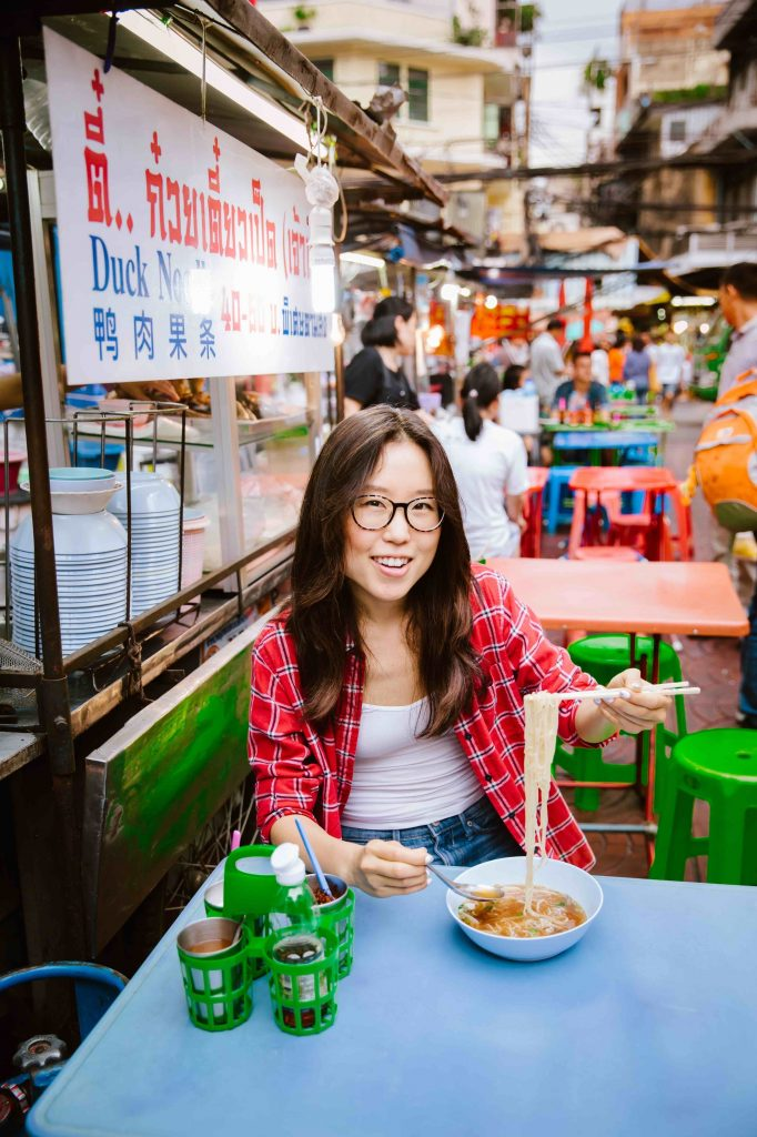 Mina Oh trying a noodle dish in Bangkok, Thailand.