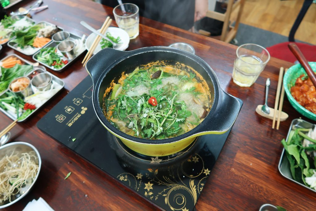 Soybean paste soup boils in a pot and on top of it is some vibrant red chili garnish.