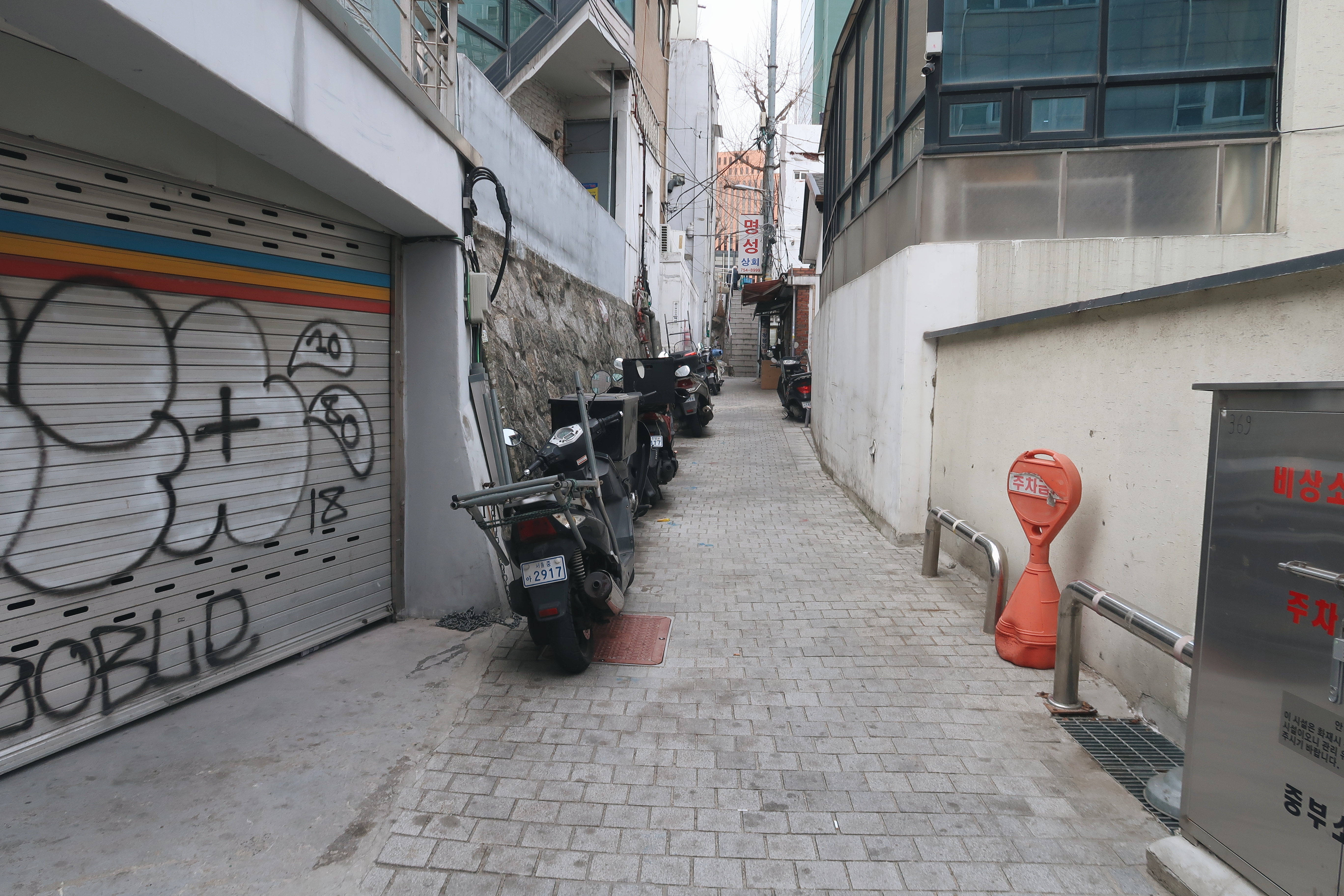 A photograph of a small street between buildings, with some grafiti on a garage door and motorcycles lining the sides (Seoul).