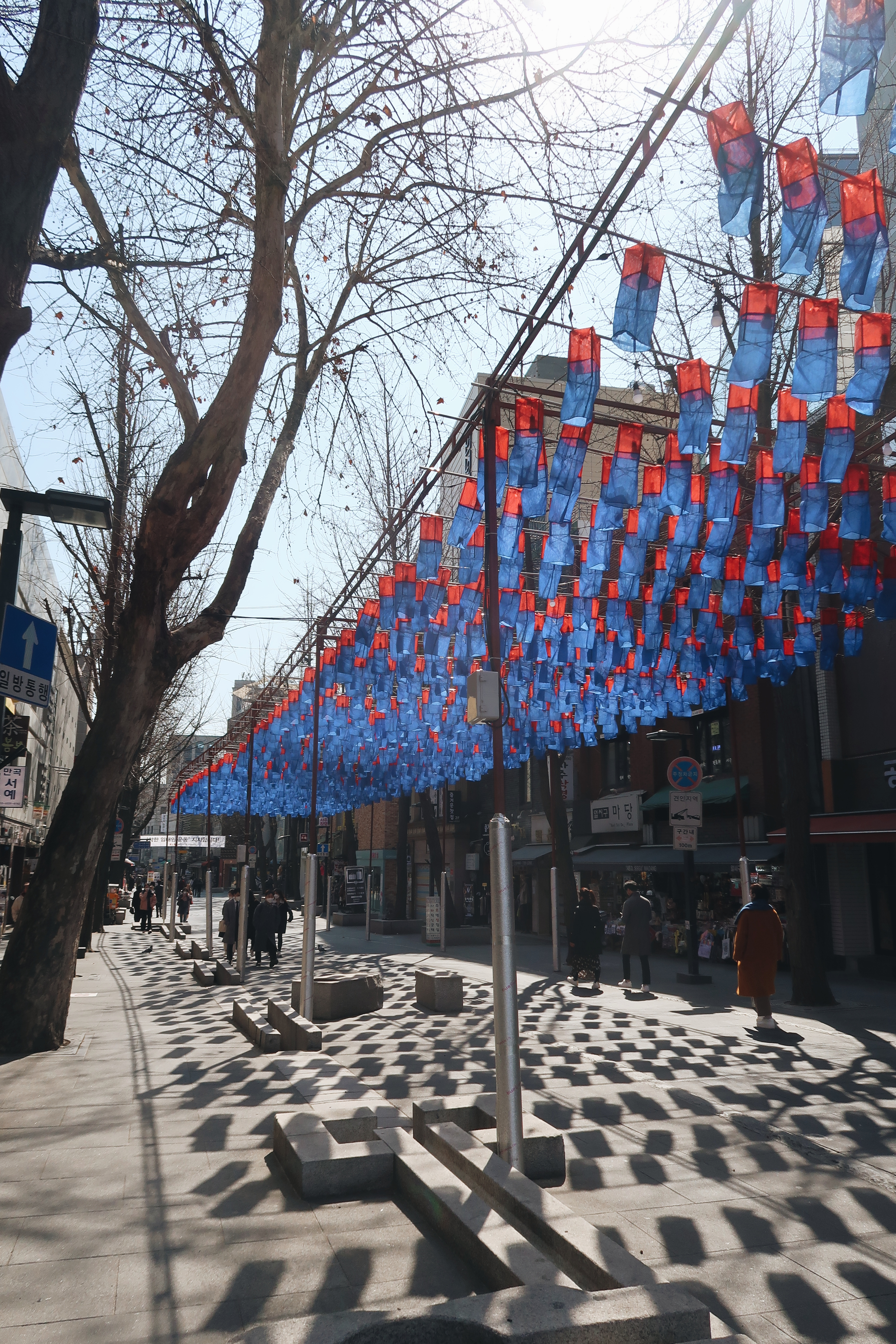 Vibrant blue and yellow lanterns hanging above a street (Seoul)