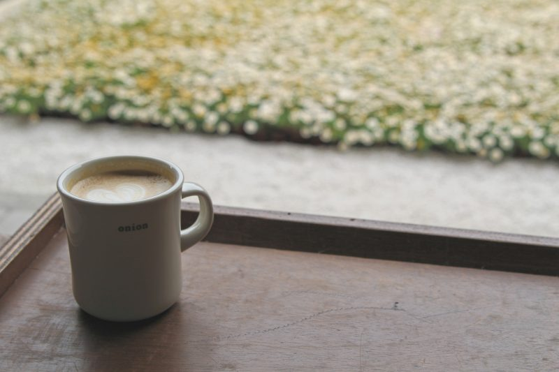 "A cup of coffee in a white mug with the word ""onion"" written on it. The backdrop is a flowerbed."