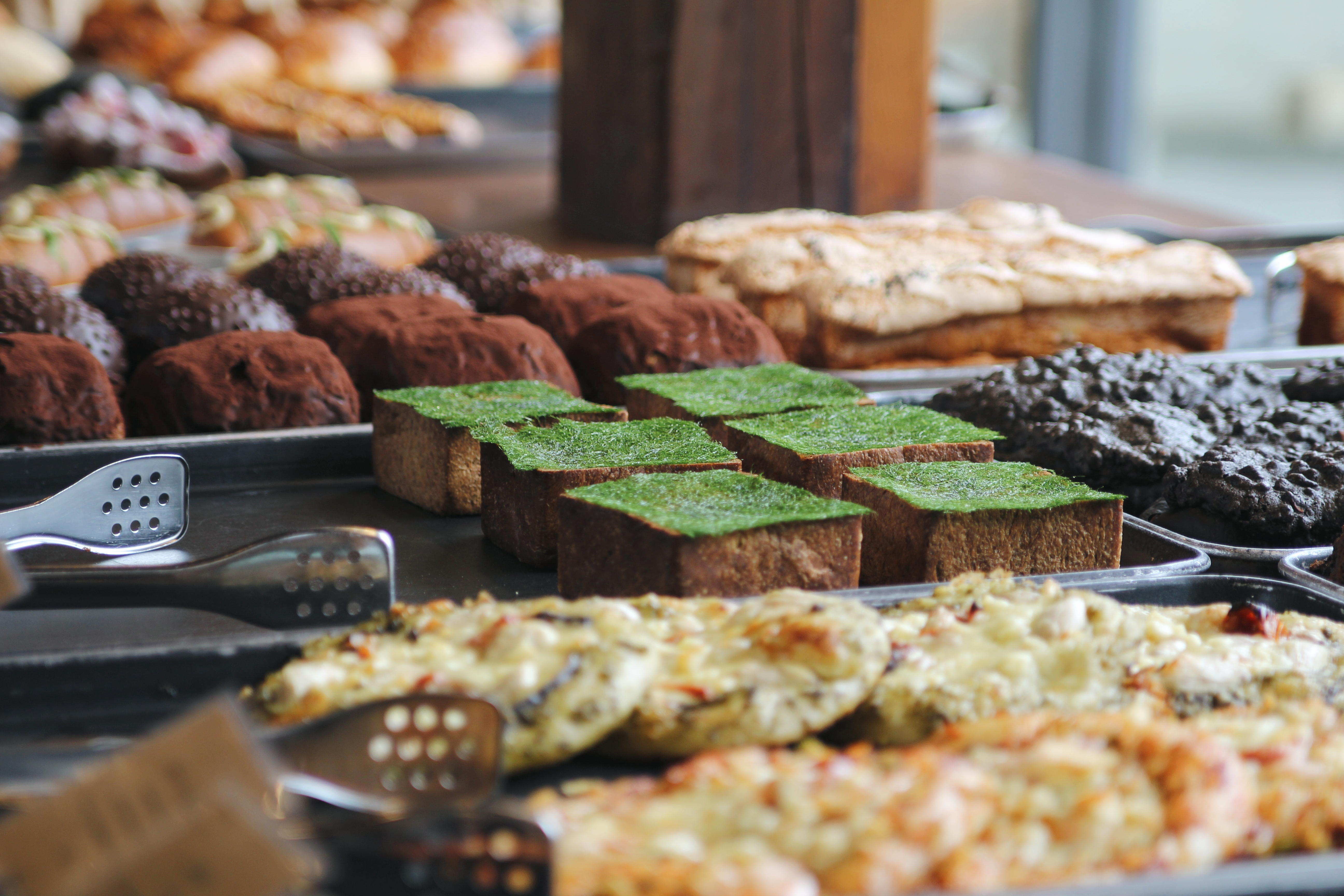 A variety of pastries at Onion. The seaweed fulvescens + Gamtae (seaweed) with honey is in focus, but it is surrounded by a variety of other pastries.