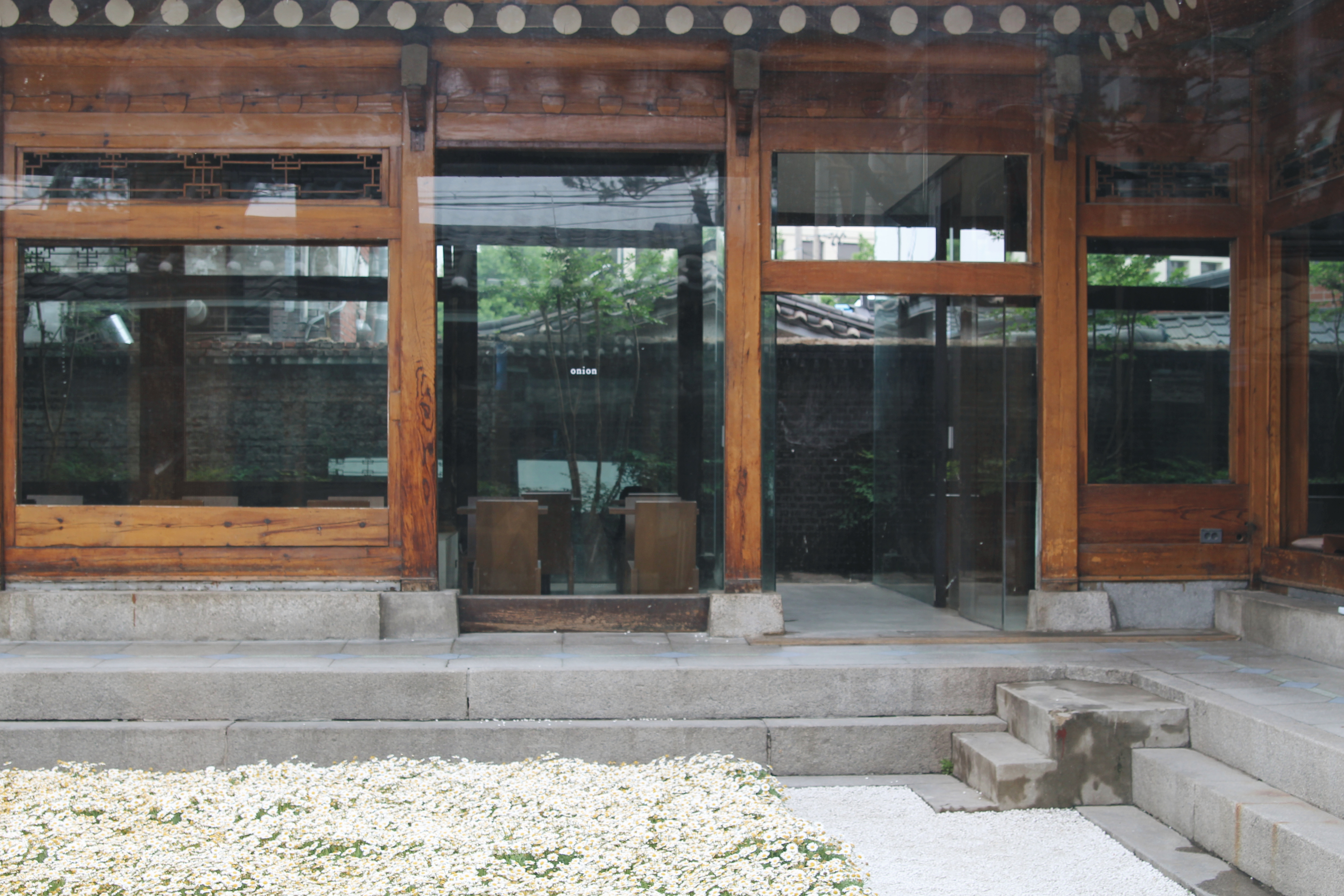 A quiet morning at Onion, so it is empty. There is a flower bed, and behind it a section for seating with tables separated by a wooden structure and glass windows.