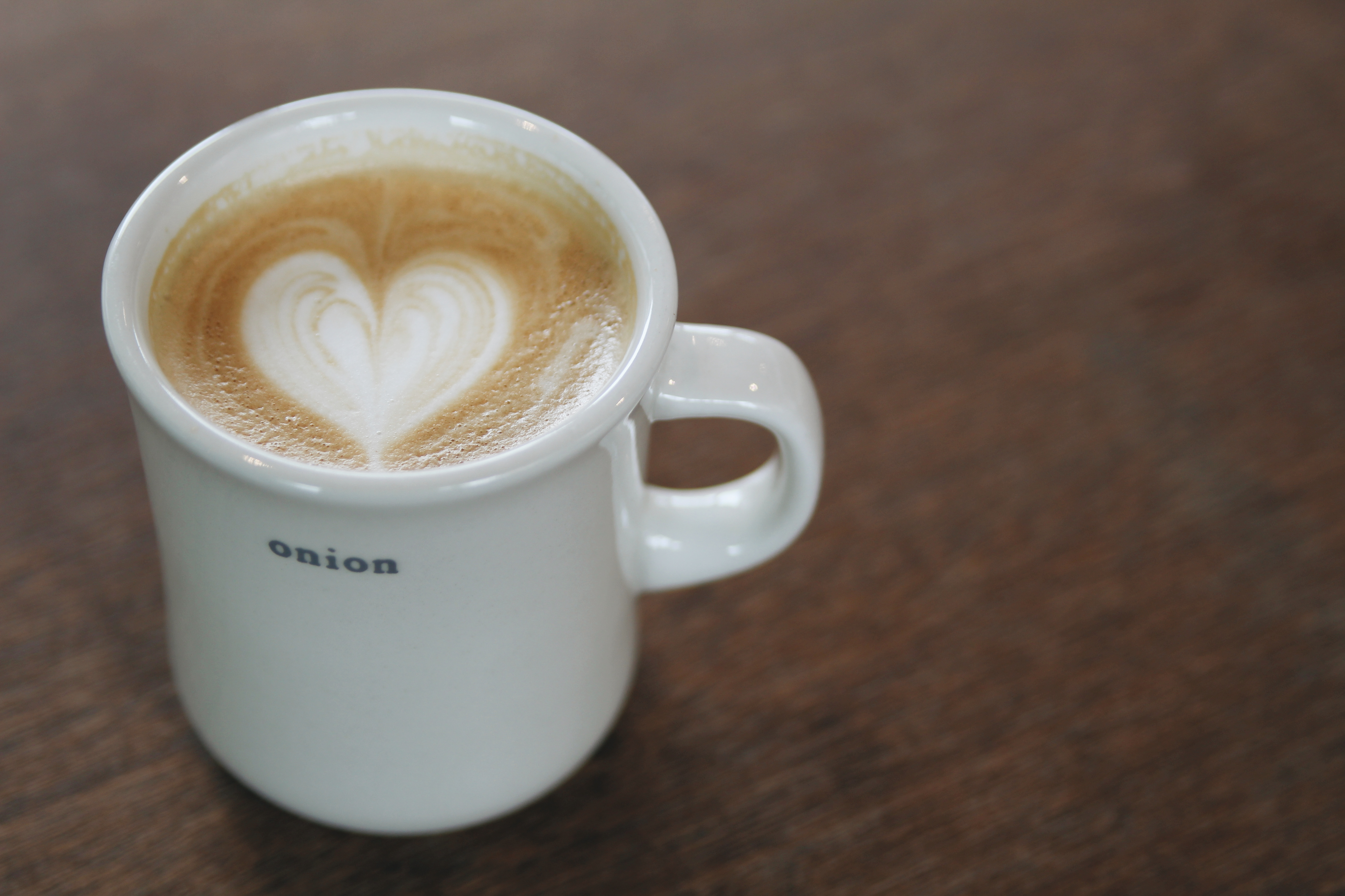 """A cafe latte in a white mug that has the word """"onion"""" written on it."""