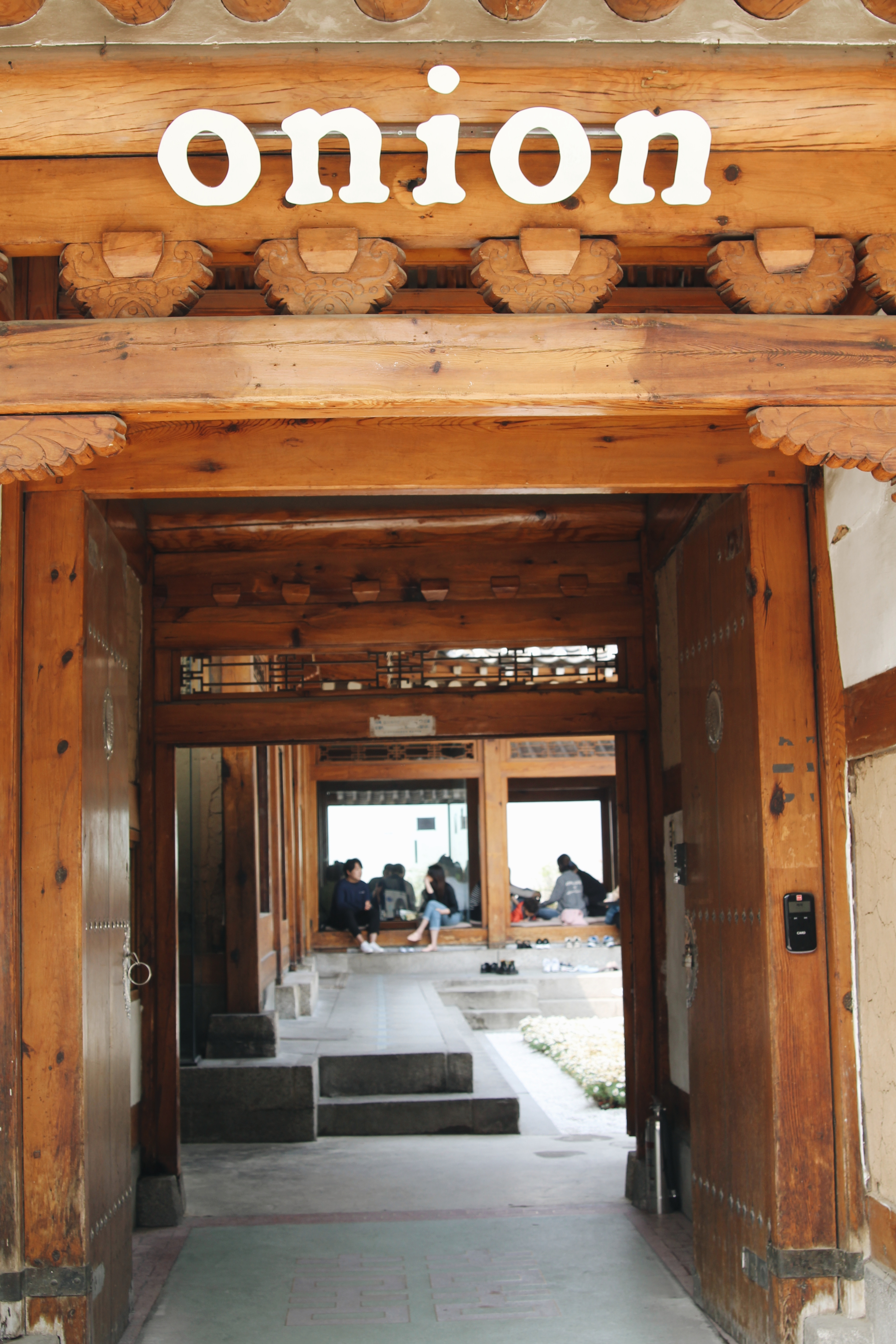 """The entrance way to Onion. You're welcomed by a traditional Korean wooden door with the word """"onion"""" written above it."""