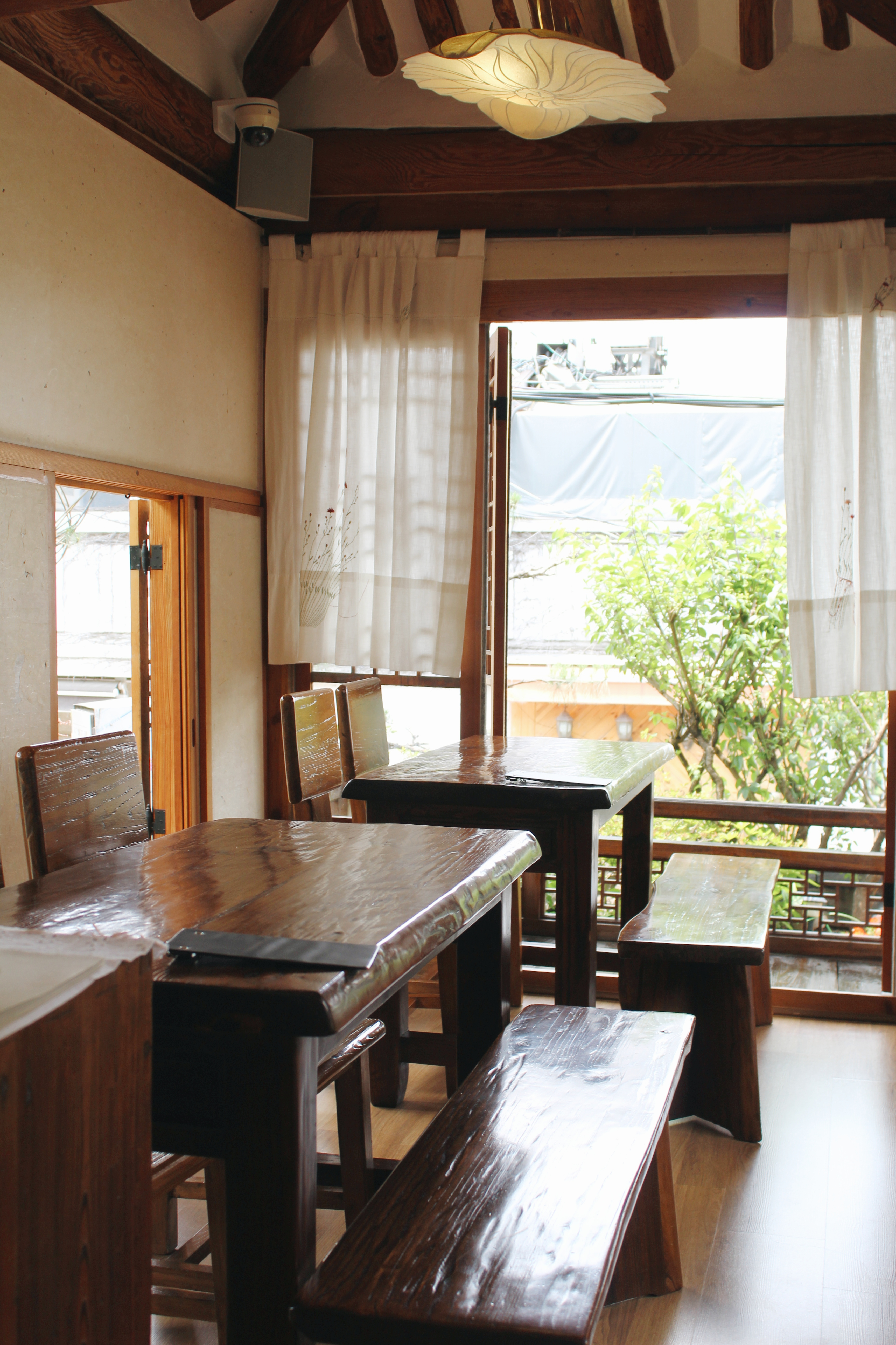 A photograph of some tables and a window with white curtains in Cha-teul.