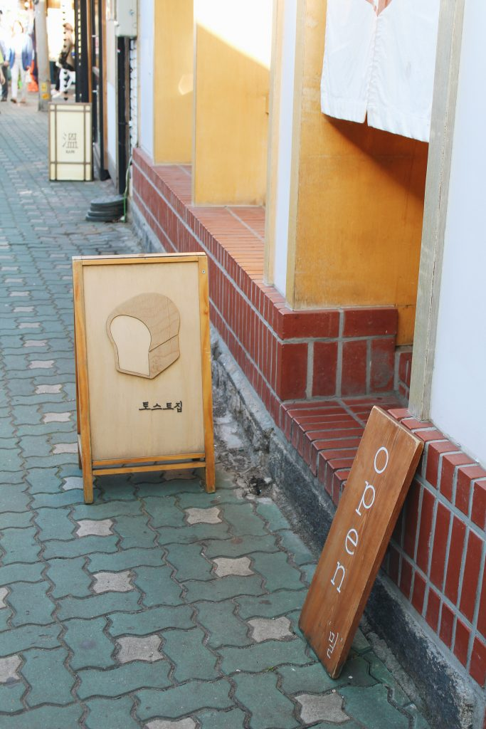 """A photo of a sign that reads 토스트 집, which directly translates to """"bread house"""". There is also another sign beside it that says """"open""""."""