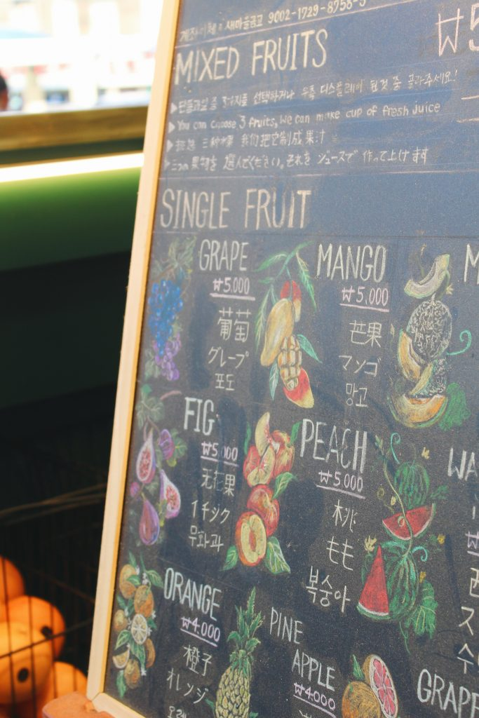 A sign at a fruit shake stand that shows what kinds of shakes there are