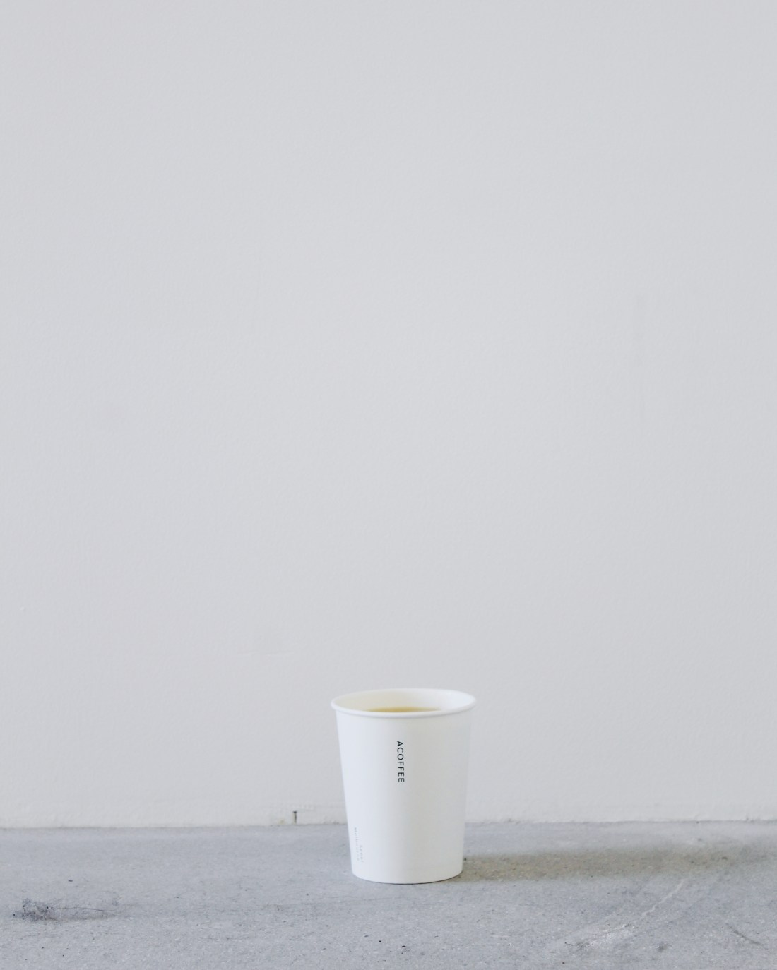 A coffee cup from ACOFFEE in front of a gray background
